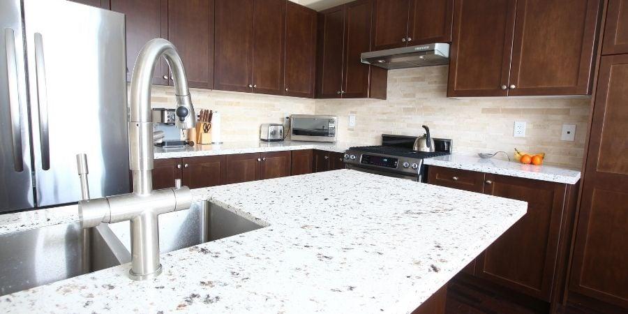 engineered white quartz countertop with dark brown cabinets