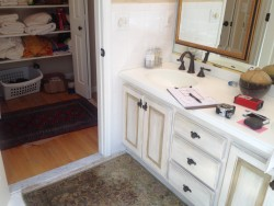 Before photo shows old vanity and linen closet.