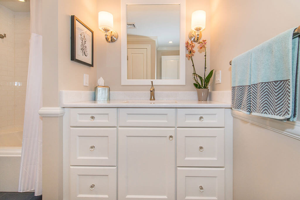 Hall bathroom remodel white vanity with quartz top and white framed mirror frame with sconces in Boonton, NJ renovated by JMC Home Improvement Specialists