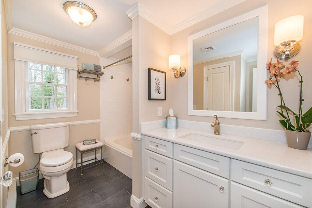 Hall bathroom remodel with white framed mirror and white vanity, shower and tub, with crown molding in Boonton, NJ renovated by JMC Home Improvement Specialists