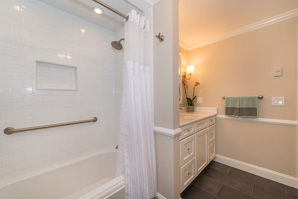 Hall bathroom remodel with white vanity, shower with subway tile, grab bar, niche, shower curtain and tub, with crown molding in Boonton, NJ renovated by JMC Home Improvement Specialists