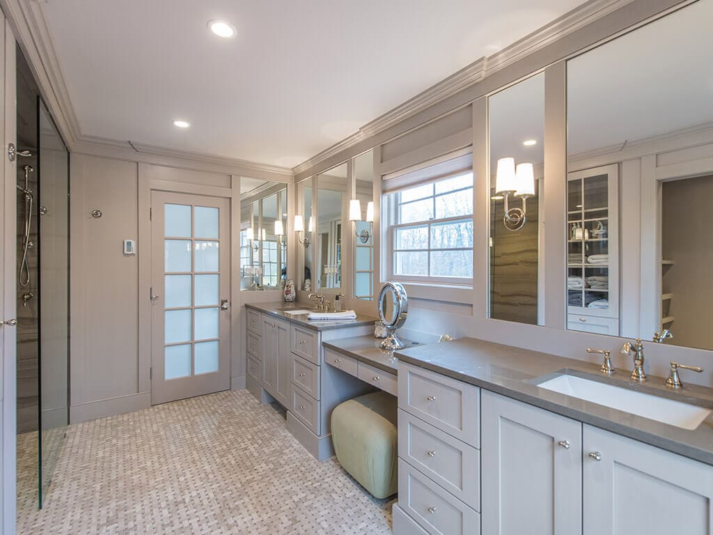 Award winning master bathroom remodel with monochromatic taupe, basket weave tile, frosted French door, make-up table, separate his and her shaker cabinet vanities, custom wood framed mirrors with sconces in Boonton, NJ renovated by JMC Home Improvement Specialists
