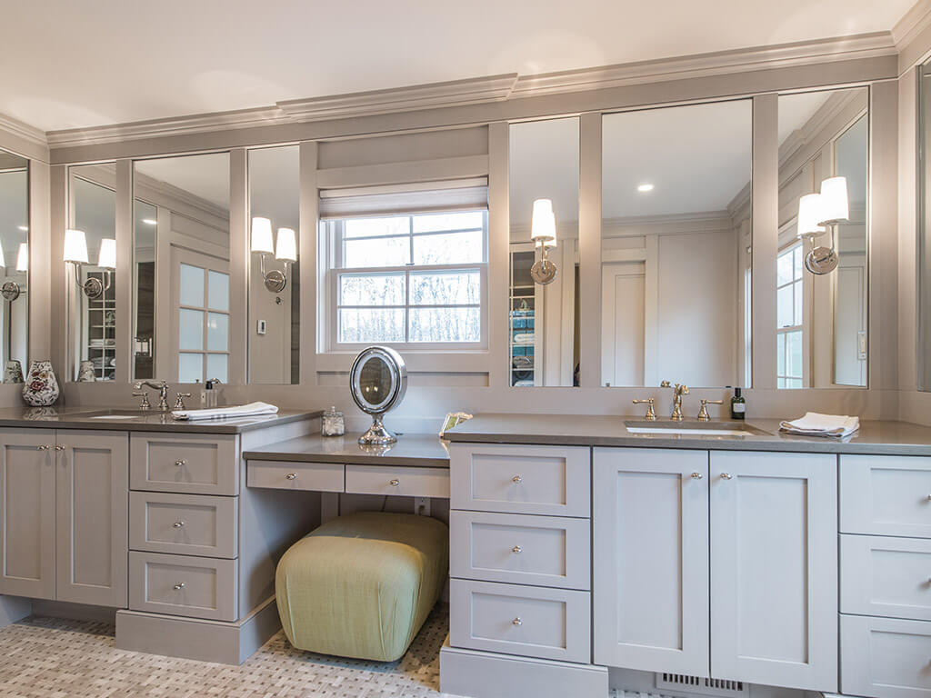 Award winning master bathroom remodel with monochromatic taupe, basket weave tile, make-up table, separate his and her shaker cabinet vanities, custom wood framed mirrors with sconces  and crown molding in Boonton, NJ renovated by JMC Home Improvement Specialists