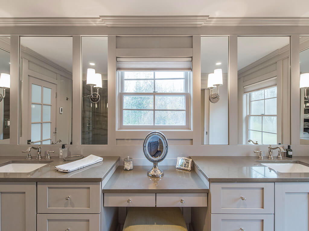 Master bathroom remodel with monochromatic taupe, basket weave tile, make-up table, separate his and her shaker cabinet vanities, custom wood framed mirrors with sconces  and crown molding in Boonton, NJ renovated by JMC Home Improvement Specialists