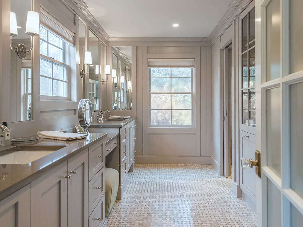 Elegant award winning master bathroom remodel with frosted glass door, separate vanities, heated basketweave floor, custom wood framed mirrors, monochromatic taupe in Boonton, NJ renovated by JMC Home Improvement Specialists