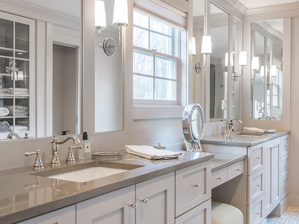 Elegant award-winning master bathroom remodel with separate vanities, rectangular undermount sinks, quartz counters, heated basketweave floor, custom wood framed mirrors, sconces in monochromatic taupe in Boonton, NJ renovated by JMC Home Improvement Specialists