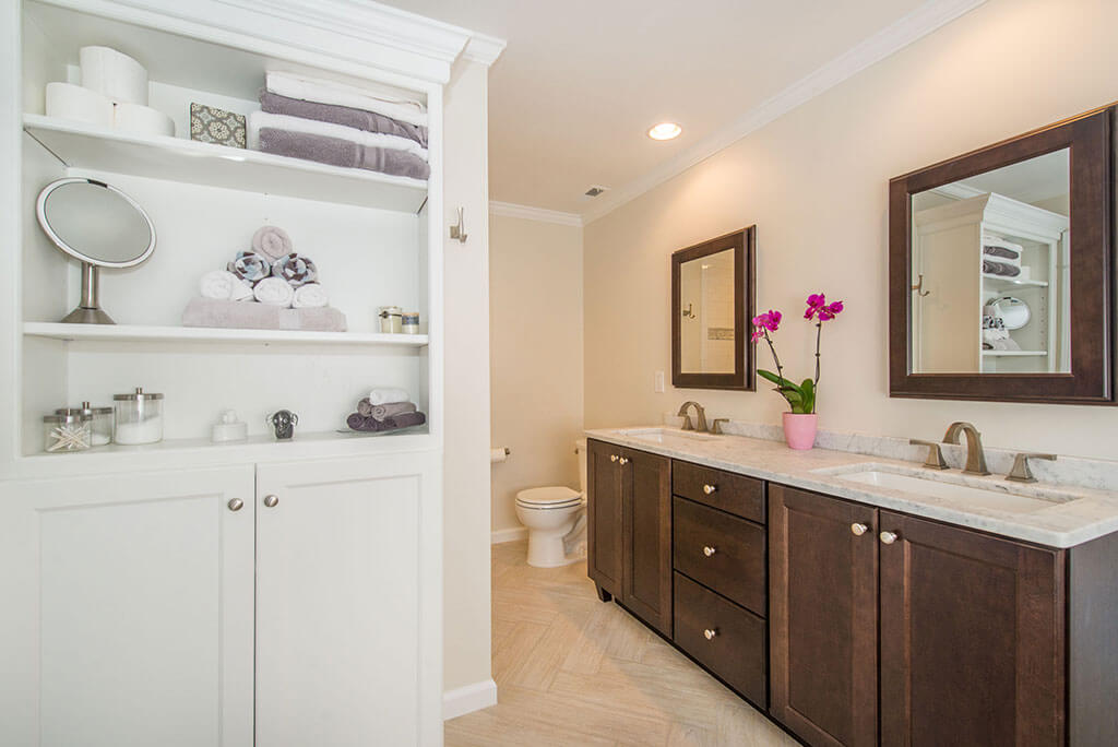 Master bathroom remodel with dark wood vanity, rectangular undermount sinks with granite counters, wood framed mirrors, white open shelving in linen cabinet in Lake Hopatcong, NJ renovated by JMC Home Improvement Specialists