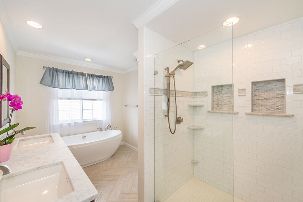 Master bathroom remodel with his and hers vanity, rectangular undermount sinks with granite counters, white shower with grey niches, clear glass shower door panel and soaking tub in Lake Hopatcong, NJ renovated by JMC Home Improvement Specialists