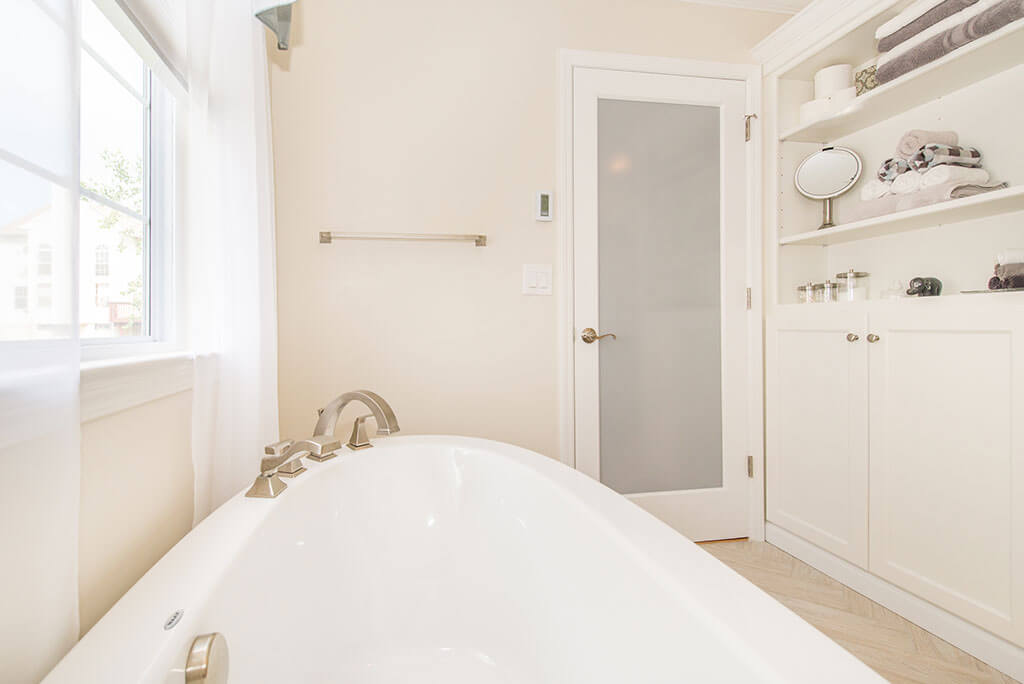 Master bathroom remodel with soaking tub, frosted glass door, open shelving and white shaker linen cabinet with brushed nickel finishes in Lake Hopatcong, NJ renovated by JMC Home Improvement Specialists