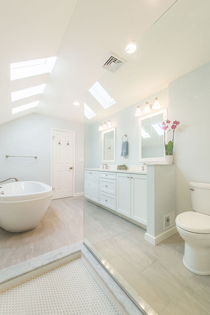 White master bathroom remodel with vaulted ceilings, natural light, his and hers vanity, white framed mirrors, clear glass shower door panel, and soaking tub in Madison, NJ renovated by JMC Home Improvement Specialists
