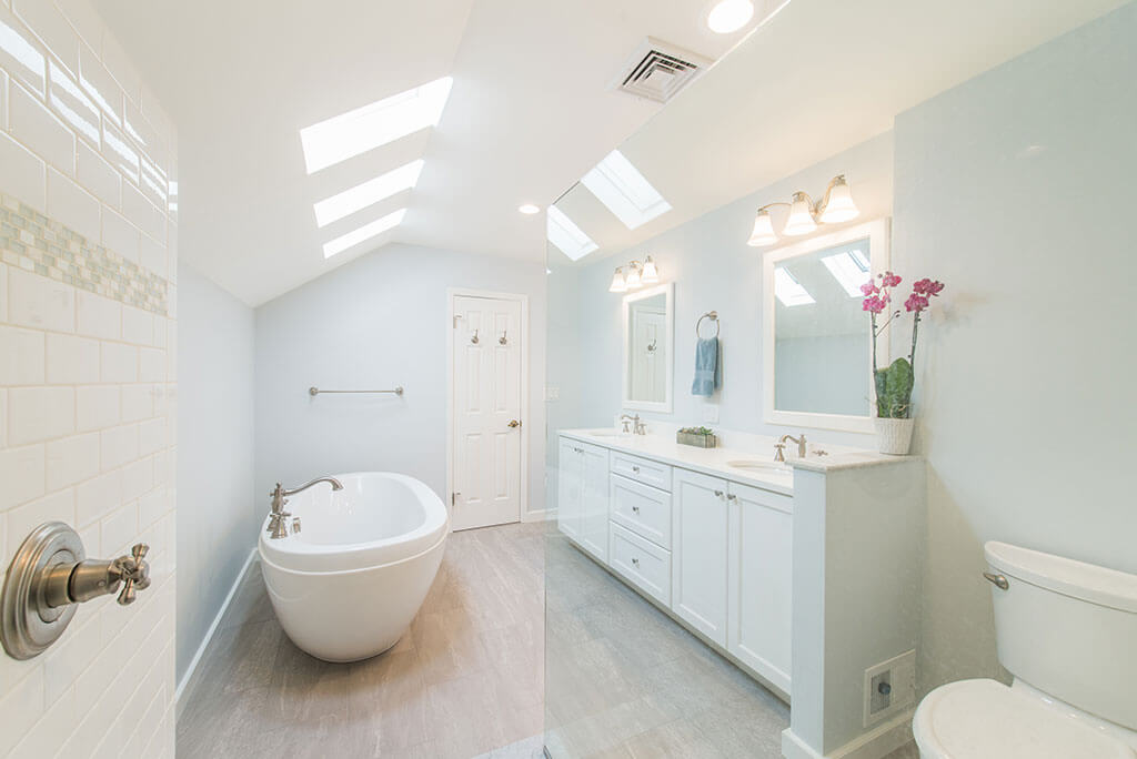 White master bathroom remodel with vaulted ceilings, skylight for natural light, his and hers vanity, white framed mirrors, clear glass shower door panel, and soaking tub in Madison, NJ renovated by JMC Home Improvement Specialists
