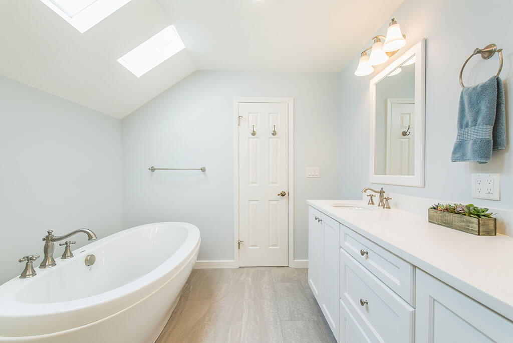White master bathroom remodel with vaulted ceilings, skylight for natural light, his and hers vanity, white framed mirrors and soaking tub in Madison, NJ renovated by JMC Home Improvement Specialists