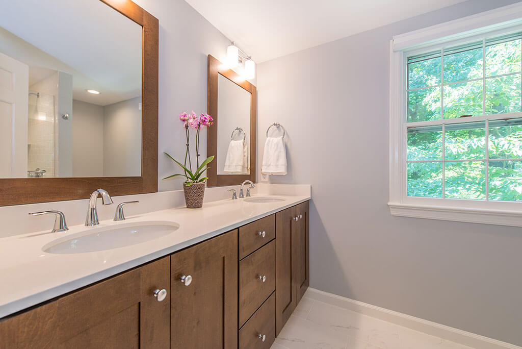 Master bathroom remodel with his and hers wood vanity, quartz counters, wood framed mirrors and chrome finishes in Mendham, NJ renovated by JMC Home Improvement Specialists