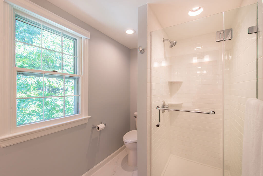 Master bathroom remodel with clear glass shower door, white subway tile and corner shelves in shower and grey painted walls in Mendham, NJ renovated by JMC Home Improvement Specialists
