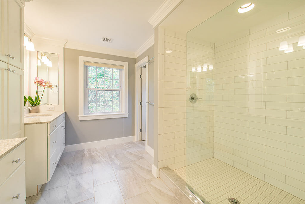 Master bathroom remodel in Morristown, NJ with white subway tile in shower with clear glass panel, quartz counters and grey painted walls with white crown molding renovated by JMC Home Improvement Specialists