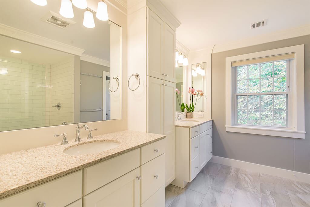 Master bathroom remodel with his and hers separate white vanities, quartz counters, linen cabinet and grey painted walls with white crown molding in Morristown, NJ renovated by JMC Home Improvement Specialists