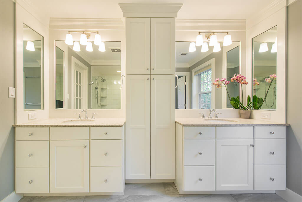 Master bathroom remodel with his and hers separate white vanities, quartz counters, linen cabinet with white crown molding in Morristown, NJ renovated by JMC Home Improvement Specialists
