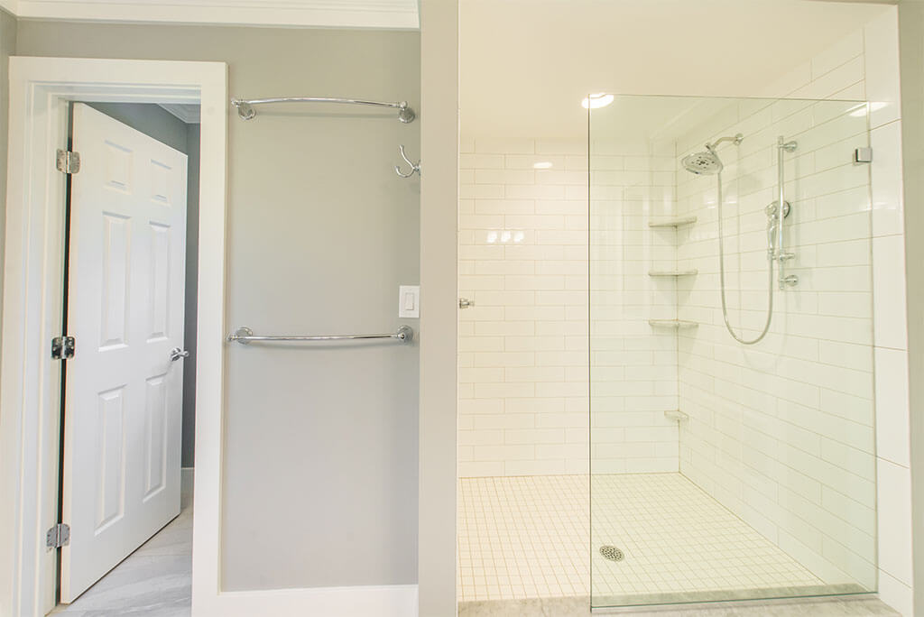 Master bathroom remodel in Morristown, NJ with curbless walk-in shower with white subway tile, clear glass panel, corner shelves, chrome finishes renovated by JMC Home Improvement Specialists