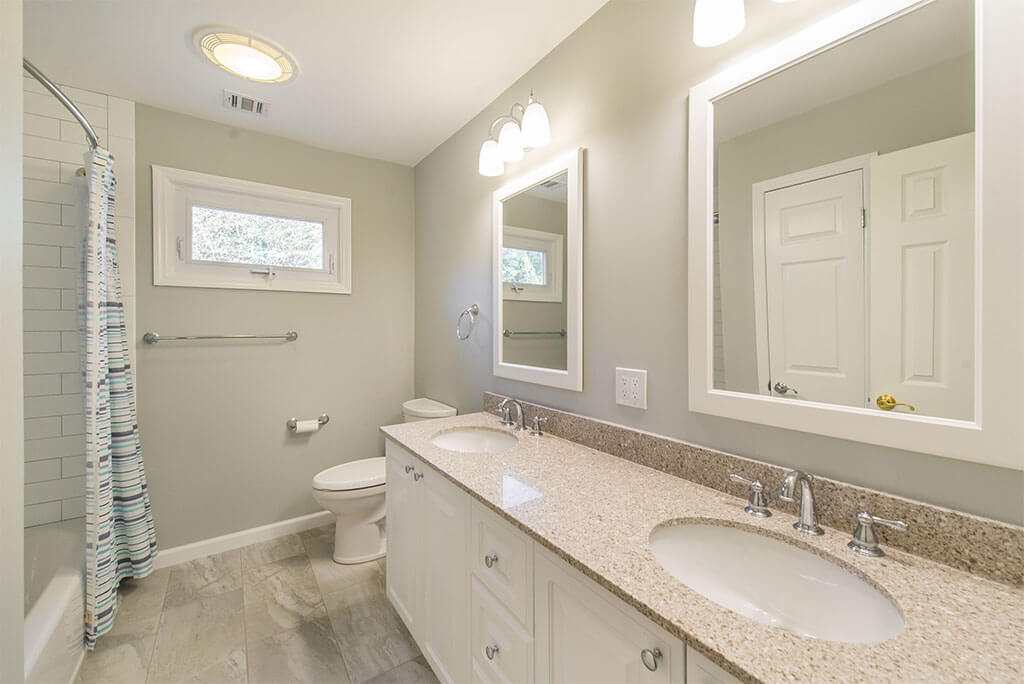 Hall bathroom remodel with his and hers white vanities, white framed mirrors, tub and curved curtain with white subway tile and grey painted walls  in Morristown, NJ renovated by JMC Home Improvement Specialists
