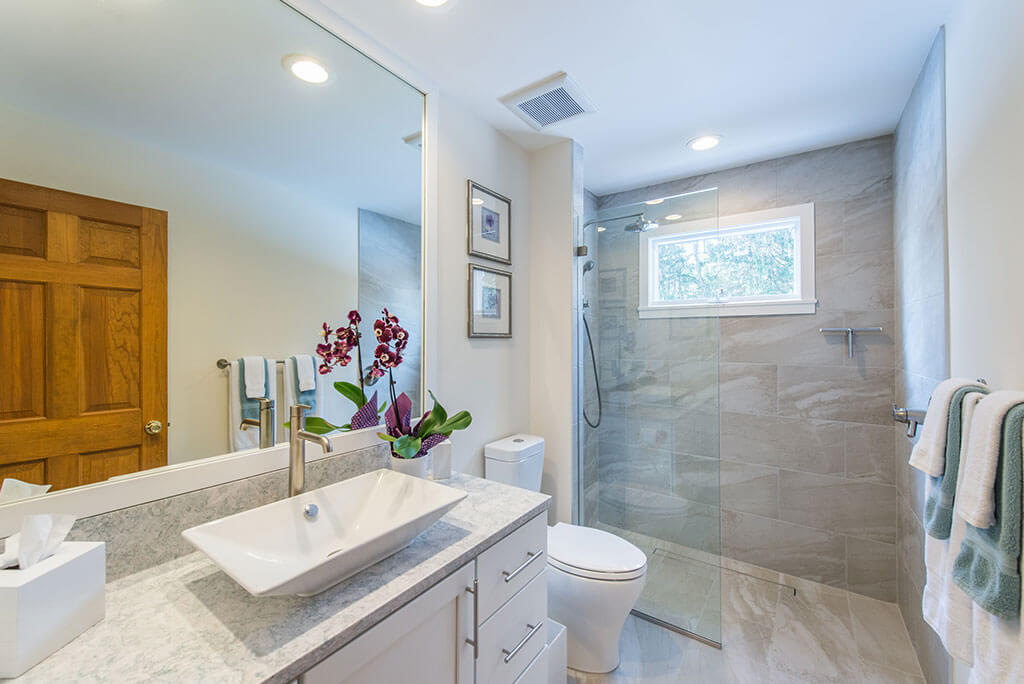Hall bathroom remodel with curbless, roll-in shower with frameless glass panel, vessel sink, quartz counter and white shaker cabinet vantity in Chester, NJ renovated by JMC Home Improvement Specialists