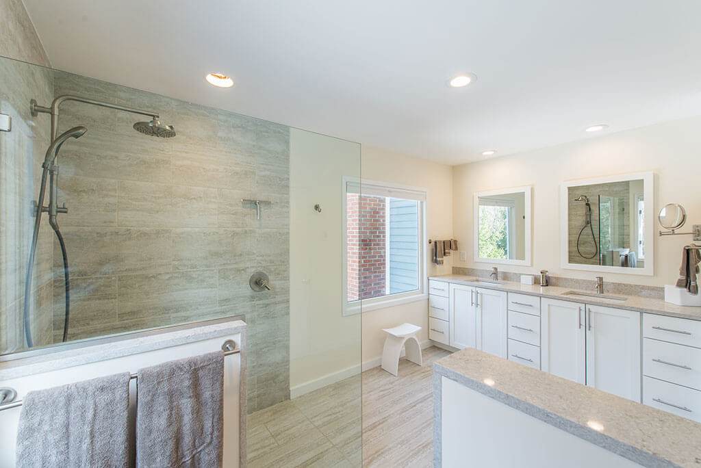 Master bathroom remodel with curbless, roll-in shower with frameless glass panel, Kohler hydro rail, half wall by toilet, white shaker his and hers vanity with quartz counters and white framed mirrors in Chester, NJ renovated by JMC Home Improvement Specialists