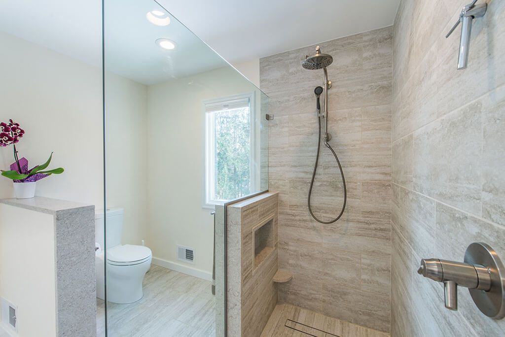 Master bathroom remodel with curbless, roll-in shower with frameless glass panel, Kohler hydro rail and skirted toilet in Chester, NJ renovated by JMC Home Improvement Specialists
