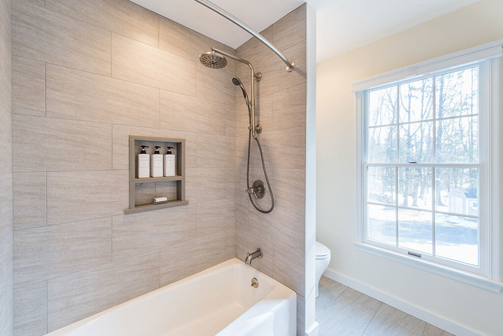 Hall bathroom remodel with tub and curved shower curtain, built in niche and grey tile in Chester, NJ renovated by JMC Home Improvement Specialists