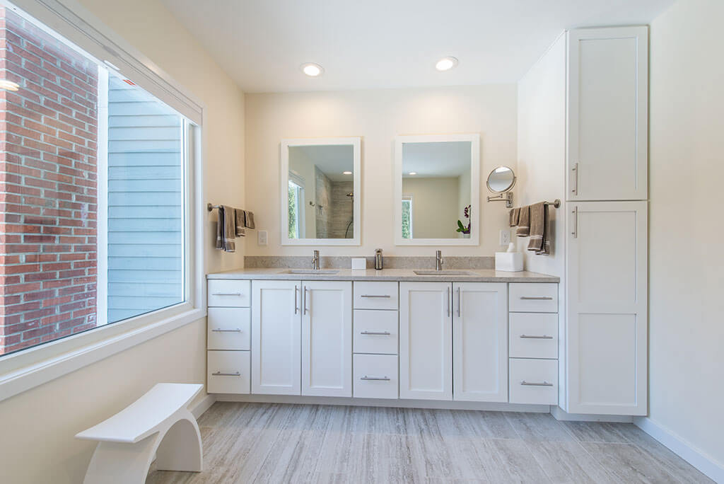 Master bathroom remodel with white shaker his and hers vanity with quartz counters and white framed mirrors, large window and linen cabinet in Chester, NJ renovated by JMC Home Improvement Specialists