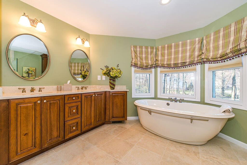 Bathroom remodel with soaking tub, triple windows, his and hers wood vanity, circle mirrors in Randolph, NJ renovated by JMC Home Improvement Specialists