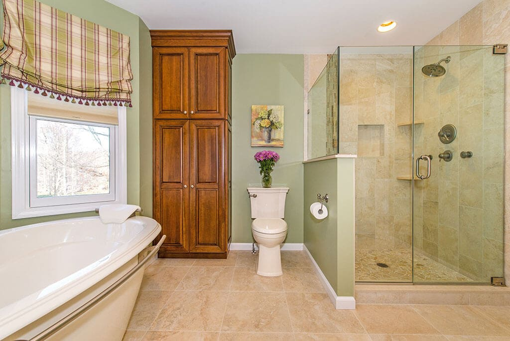 Bathroom remodel with soaking tub, linen cabinet, frameless clear glass shower door with niche and corner shelves in shower with green painted walls in Randolph, NJ renovated by JMC Home Improvement Specialists