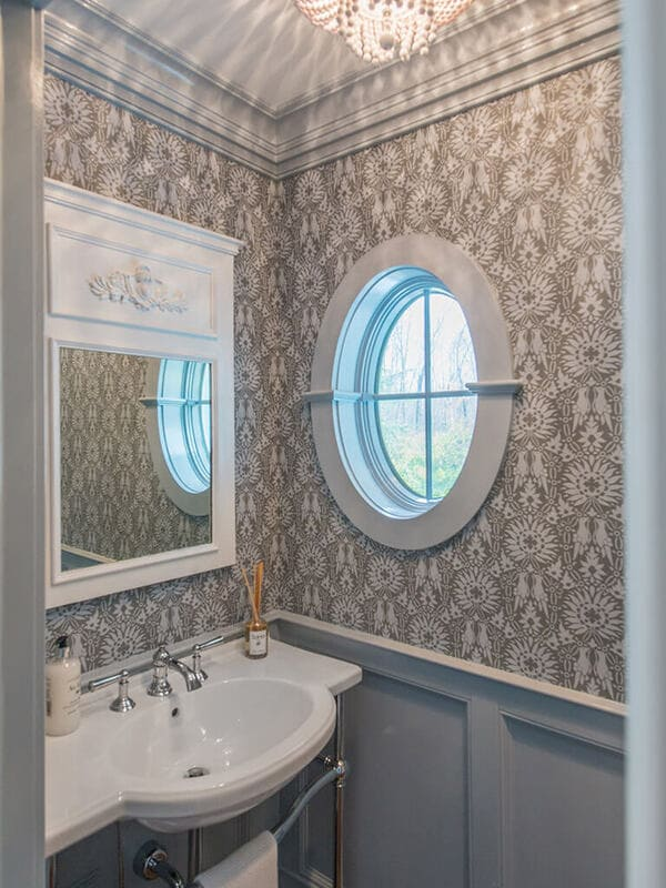 Powder room with wall panels, crown molding, retro pedestal sink with chrome legs, decorative white mirror, chandelier, Farrow & Ball paint and paper and oval window in Morris County, NJ renovated by JMC Home Improvement Specialists
