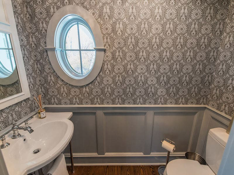 Powder room with wall panels, crown molding, retro pedestal sink with chrome legs, decorative white mirror, chandelier, Farrow & Ball paint and paper and oval window in Boonton, NJ renovated by JMC Home Improvement Specialists
