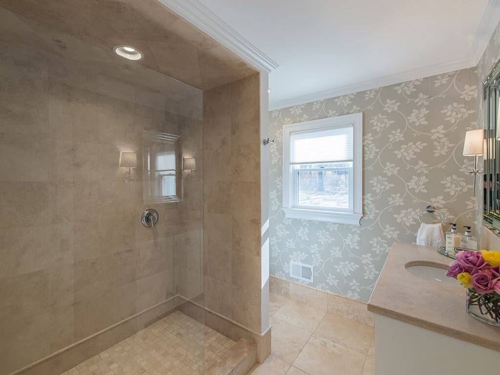 Hall bathroom remodel with decorative wallpaper, crown molding, glass panel shower door and free standing vanity in Boonton, NJ renovated by JMC Home Improvement Specialists