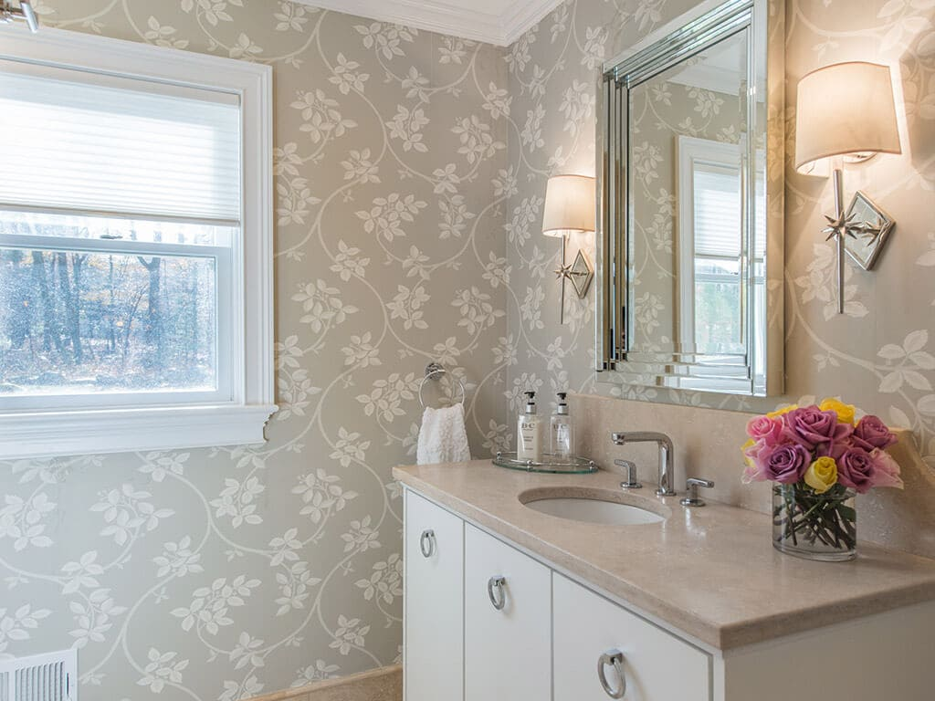 Hall bathroom remodel with decorative wallpaper, crown molding, free standing vanity with flush white doors and framed mirror in Boonton, NJ renovated by JMC Home Improvement Specialists