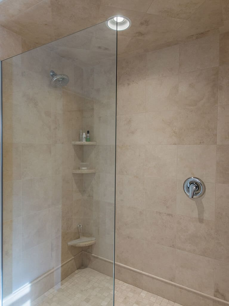 Hall bathroom remodel glass panel shower door with corner shelves and chrome finishes in Boonton, NJ renovated by JMC Home Improvement Specialists