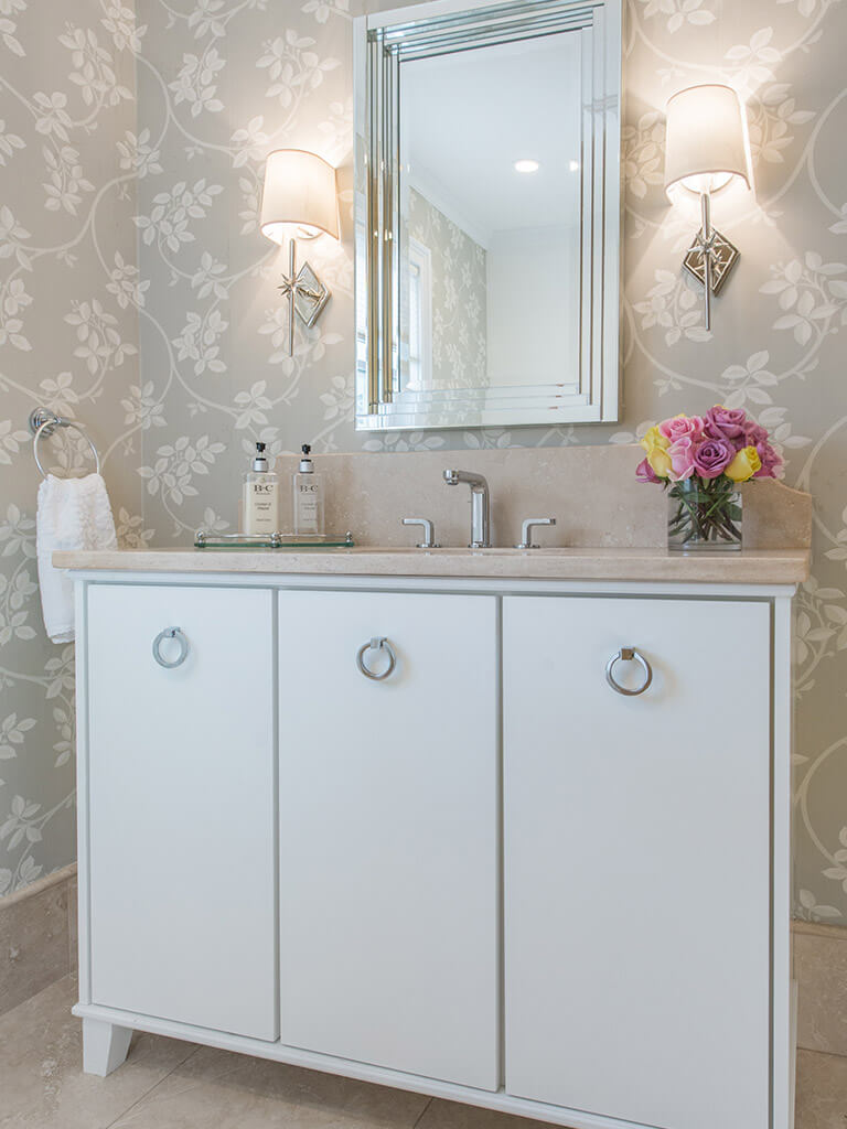 Hall bathroom remodel with decorative wallpaper, marble, free standing vanity with flush white doors, framed mirror, decorative lighting and chrome finishes in Boonton, NJ renovated by JMC Home Improvement Specialists