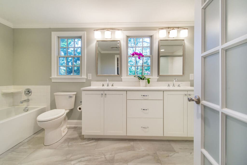 White bathroom remodel with French door, dual vanity, tub, chrome finishes and grey walls in Springfield, NJ renovated by JMC Home Improvement Specialists