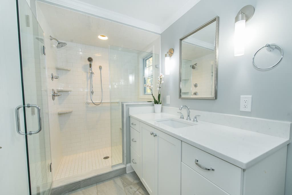 White bathroom remodel with chrome finishes and grey walls, white vanity, quartz counter, white subway tiles in shower with framless shower door in Springfield, NJ renovated by JMC Home Improvement Specialists