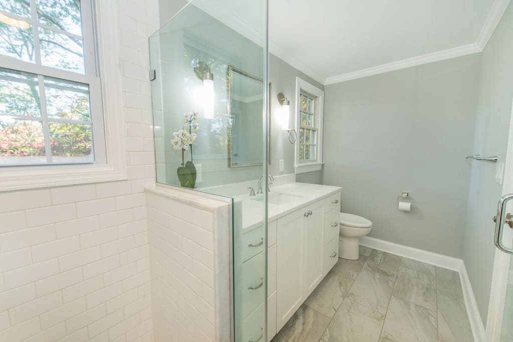 Bathroom remodel with white subway tiles in shower framing window with chrome finishes, white vanity with quartz counter and decorative framed mirror in Springfield, NJ renovated by JMC Home Improvement Specialists