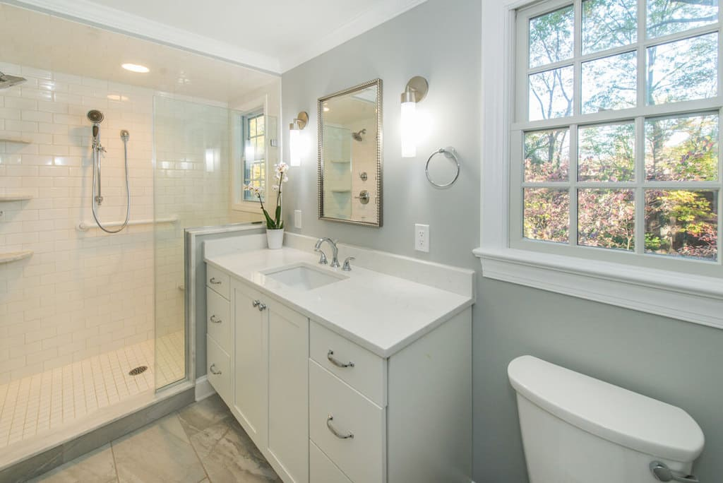 White bathroom remodel with white subway tiles in shower, marble corner shelves, grab bar, chrome finishes, white shaker cabinet vanity with quartz counter and decorative framed mirror with sconces in Springfield, NJ renovated by JMC Home Improvement Specialists