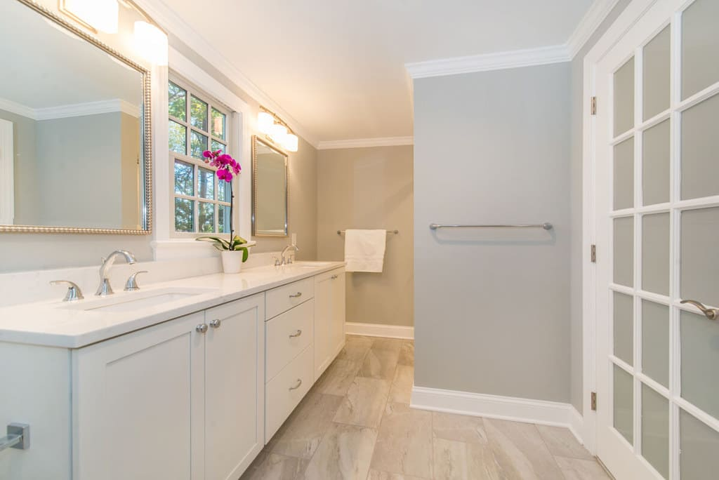 White bathroom remodel with frosted glass french door, chrome finishes and grey walls, dual white vanity, quartz counter, undermount sinks, decorative mirrors in Springfield, NJ renovated by JMC Home Improvement Specialists