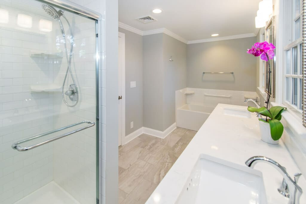 White bathroom remodel with chrome finishes and grey walls with white crown molding, dual white vanity, quartz counter, undermount sinks, shower with white subway tile, separate tub in Springfield, NJ renovated by JMC Home Improvement Specialists