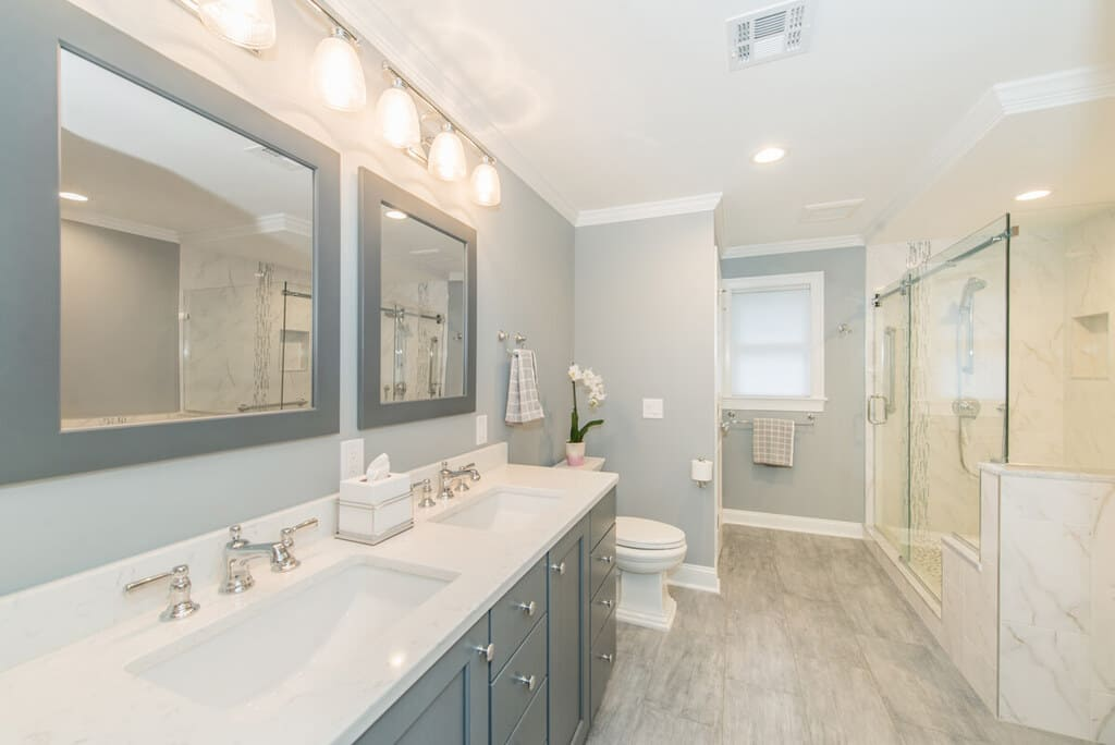 Grey and white bathroom remodel with dual undermount sink vanity with shaker cabinets, grey wood framed mirrors, frameless sliding shower door with Carrera marble in Randolph, NJ renovated by JMC Home Improvement Specialists