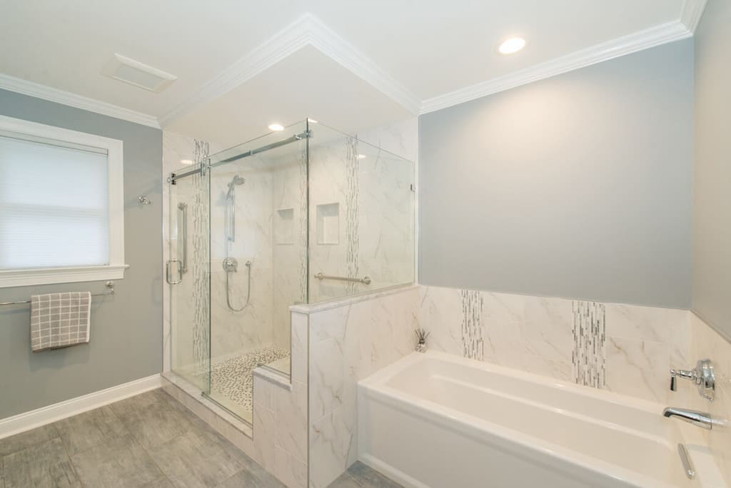 Grey and white master bathroom remodel with crown molding, Kohler accessories, frameless sliding shower door with Carrera marble, bench seat, niche, basketweave shower floor, separate soaking tub and LED highhats in Randolph, NJ renovated by JMC Home Improvement Specialists