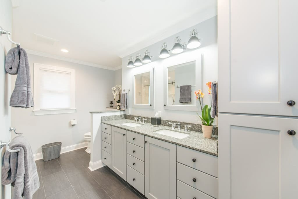 Grey and white bathroom remodel with dual undermount sink vanity with shaker cabinets, white wood framed mirrors in Randolph, NJ renovated by JMC Home Improvement Specialists
