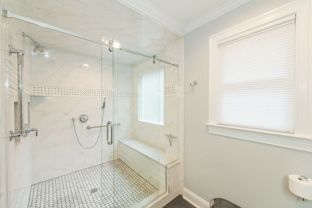 Grey and white master bathroom remodel with farmless shower door, Carrera marble, grab bars, bench seat with handheld shower, basketweave tile floor in Randolph, NJ renovated by JMC Home Improvement Specialists