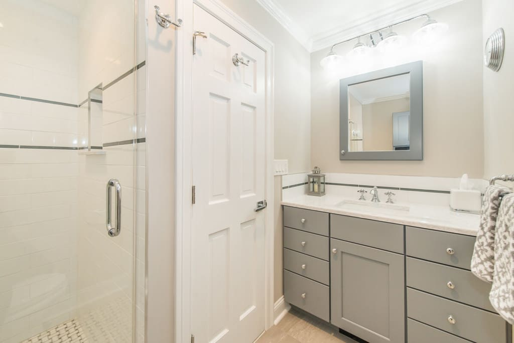 Grey and white hall bathroom remodel with undermount sink vanity and grey shaker cabinets, grey wood framed mirror, frameless shower door with subway tile and accent stripe with niche and basketweave shower floor in Randolph, NJ renovated by JMC Home Improvement Specialists