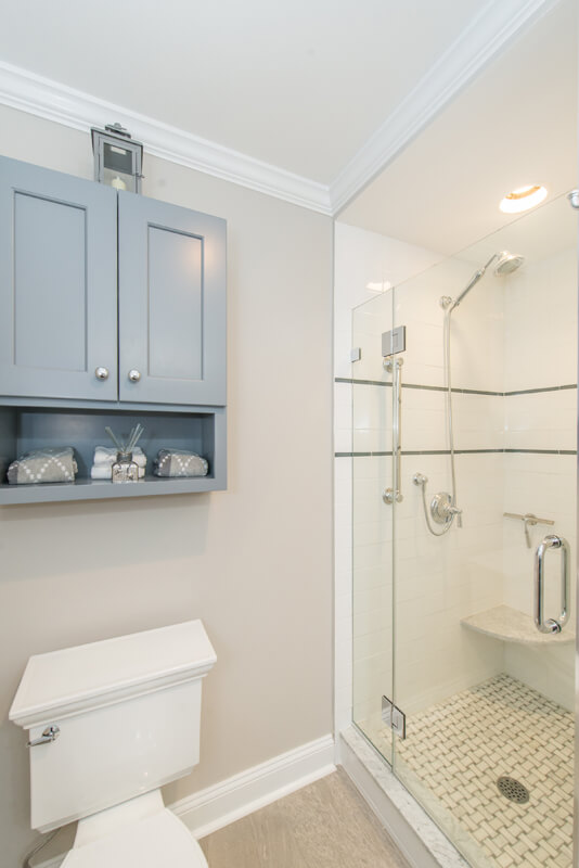 Grey and white hall bathroom remodel with Kohler accessories, grey shaker tank topper cabinet, frameless shower door with subway tile and accent stripe with niche, corner shelf and basketweave shower floor in Randolph, NJ renovated by JMC Home Improvement Specialists