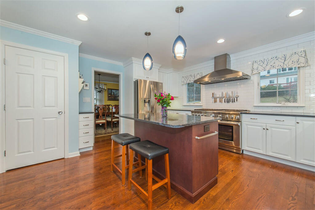 Two tone kitchen remodel with hardwood flooring, white shaker cabinets, crown molding, cherry island with granite counters, pendant lighting above island and LED highhats, subway tile backsplash, freestanding hood in Bernardsville, NJ renovated by JMC Home Improvement Specialists