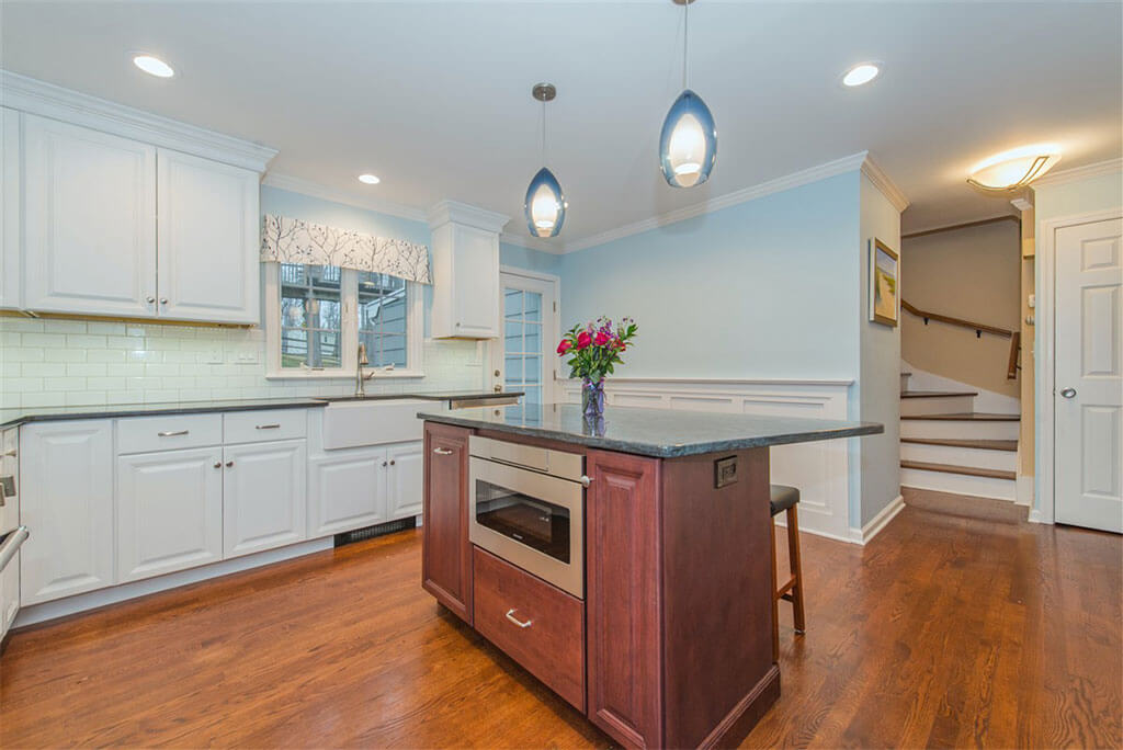 Two tone kitchen remodel with hardwood flooring, white shaker cabinets, crown molding, cherry island with granite counters, built in microwave, pendant lighting and LED highhats, subway tile backsplash, freestanding hood in Bernardsville, NJ renovated by JMC Home Improvement Specialists